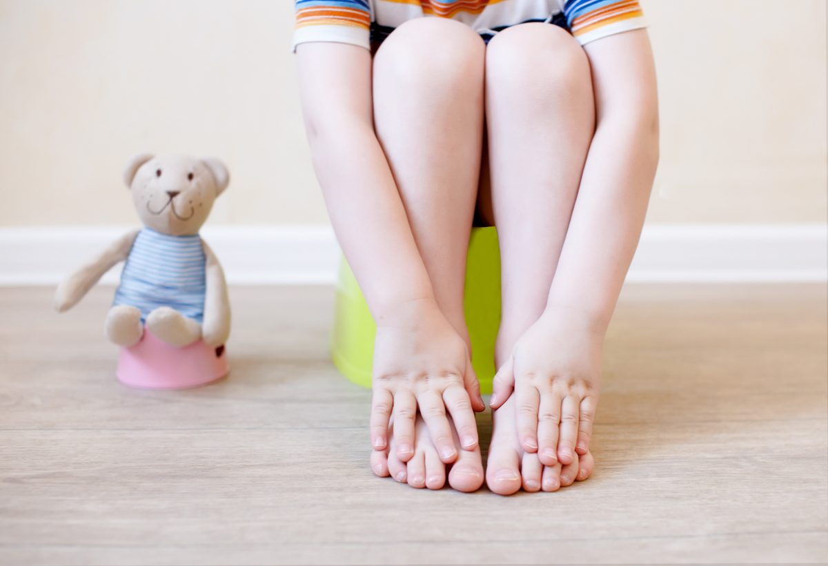 closeup of legs of the child sitting on the potty. the idea of training the child to the potty with a toy bear, which also sits on a toy potty